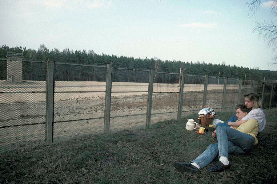 Couple From The West Having Picnic At The Border To The North Of East Berlin. Left The Watchtower, Where Border Guards From The East Are Watching The Wall. The Photograph Was Taken From The West Side, 1986 © Ann-Christine Jansson